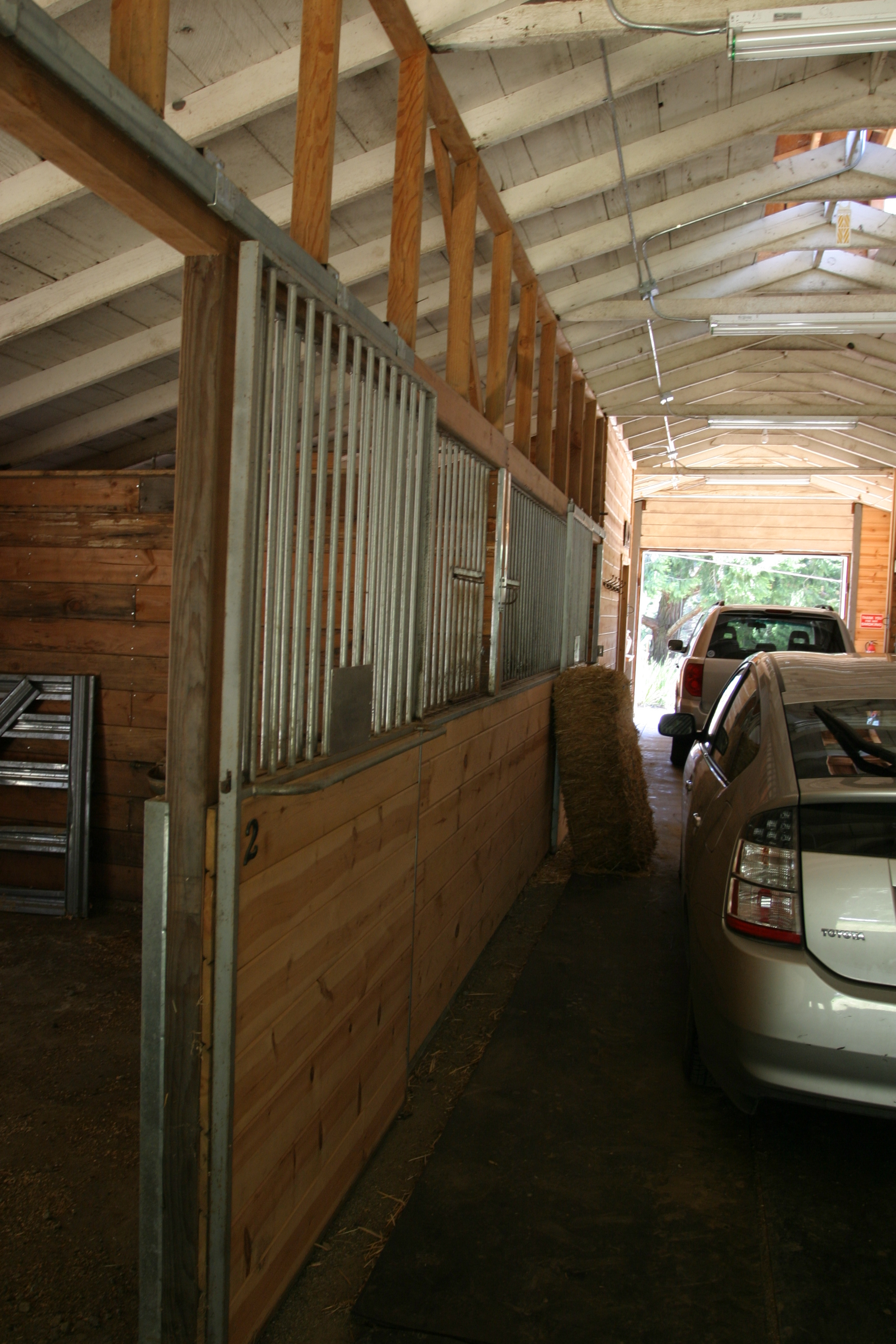 Inside horse barn and parked cars